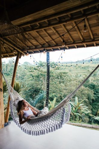 female traveler resting in hammock while contemplating with nature