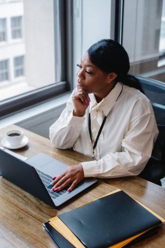 pensive woman working on laptop in modern workplace