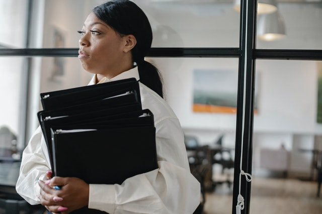 black woman carrying documents in the office