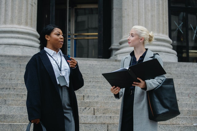 women in corporate attire talking