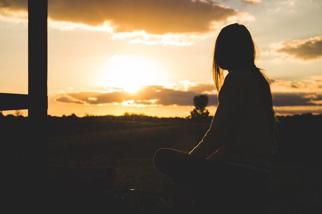 silhouette photo of woman sitting near trees during golden hour