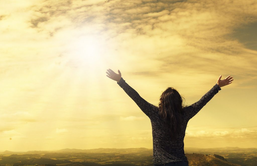 woman raising both hands to the sky
