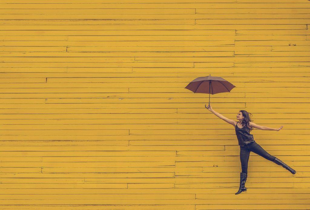 jumping woman holding an umbrella