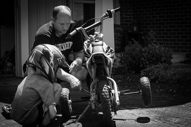 dad with his son fixing bike
