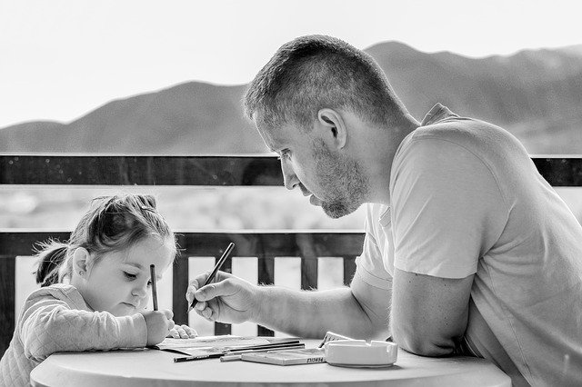dad teaching his daughter how to write