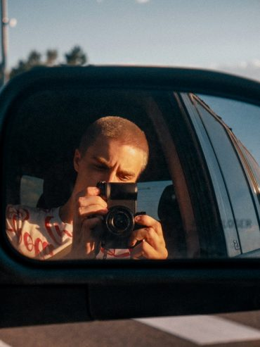 a man takes a photo reflection of a vehicle side mirror