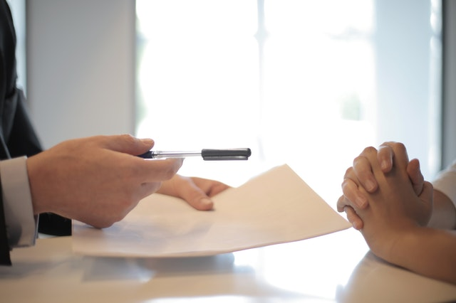 crop man giving contract to woman to sign