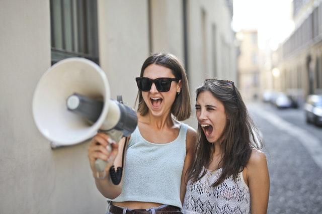 cheerful women screaming into loudspeaker
