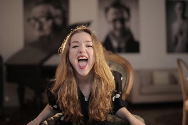 woman in black polka dots shirt sitting on chair shouting