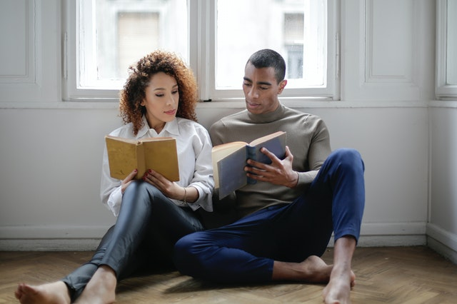 couple sitting on the floor reading book