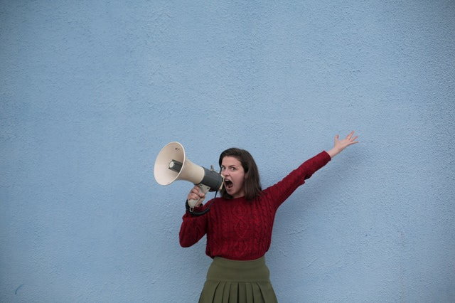 angry woman yelling into loudspeaker on blue background