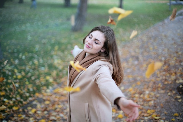 woman in open arms smiling while eyes are close