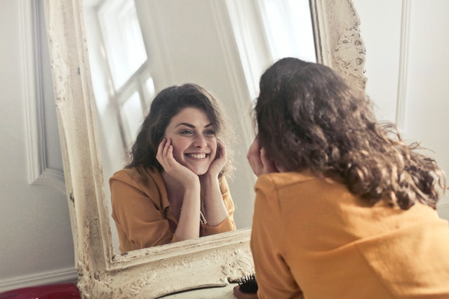 smiling woman looking at the mirror