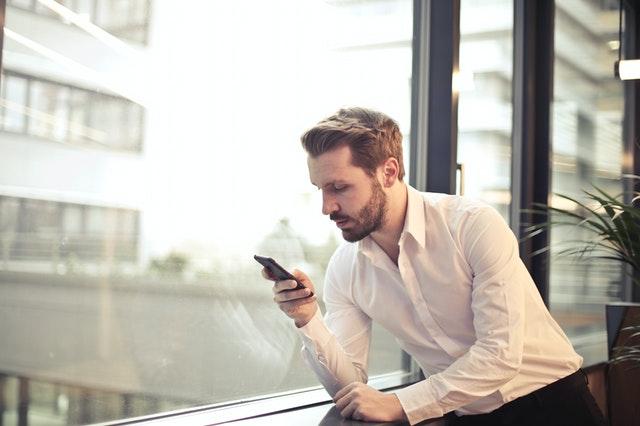 man near the window texting