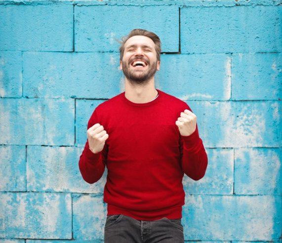 man in red crew neck sweatshirt smiling