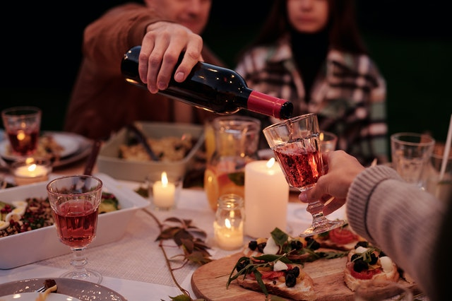crop man pouring wine to people on family dinner