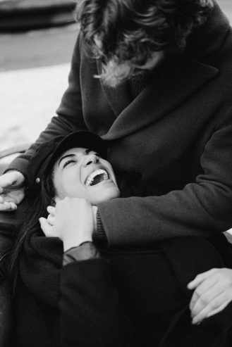 monochrome photo of woman lying on man's lap while laughing