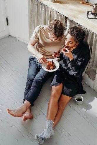 couple eating pancake on white wooden floor