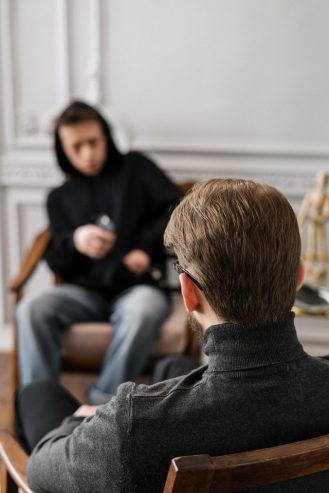 man in gray hoodie sitting on couch