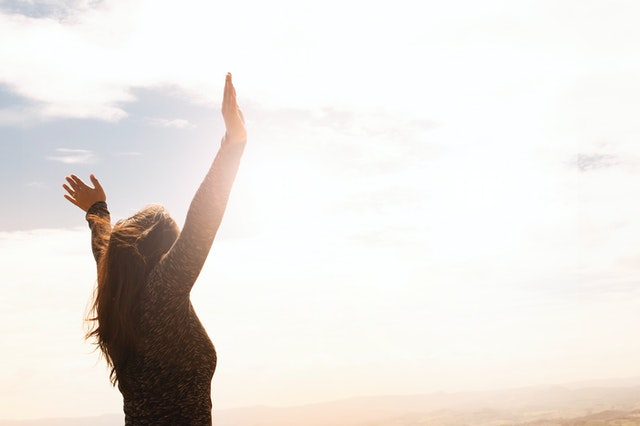 photo of a woman raising both hands
