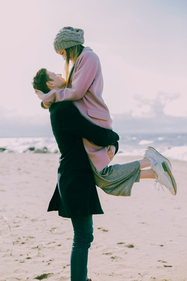 man in gray coat carrying a woman wearing pink coat near the beach