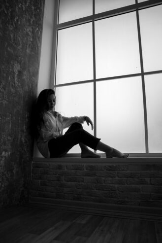 young unhappy woman sitting in solitude near window