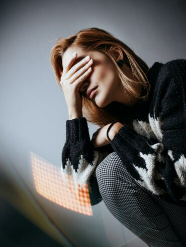 distressed upset woman covering eyes with hand