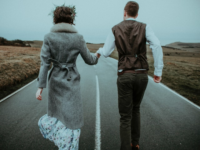 couple running on the road while holding hands