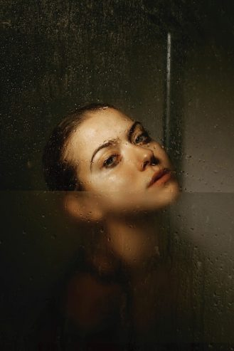 woman behind glass wall in shower cabin