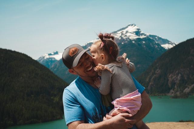 man carrying her daughter smiling