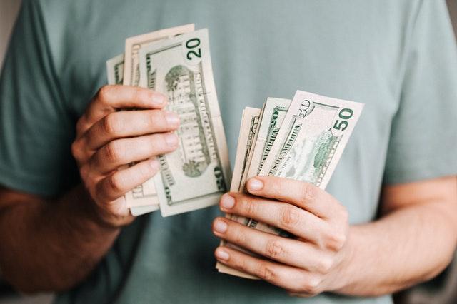 man counting dollar banknotes