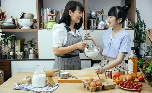 Asian mother and daughter happily discussing recipe at the kitchen