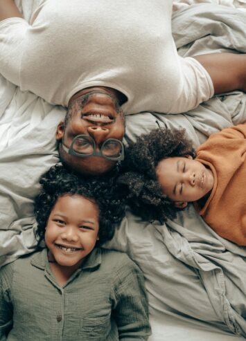 happy African American siblings with father lying on bed