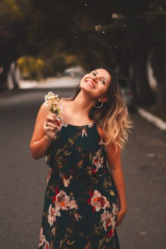 woman wearing a floral dress holding a flower
