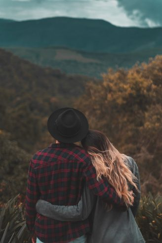 couple standing on top of a hill