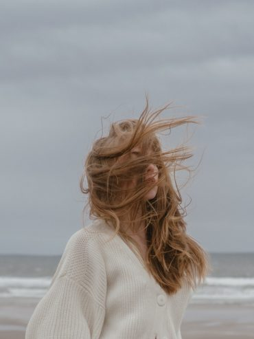 woman with windy hair on the seashore