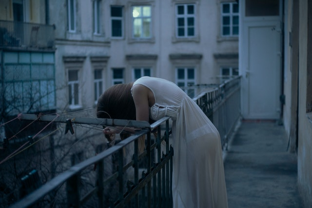 woman leaning on a railing with head down