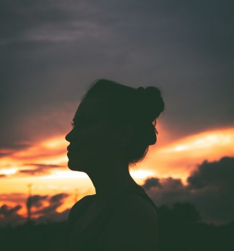 silhouette of woman resting on street during sundown
