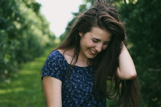 woman holding her hair smiling