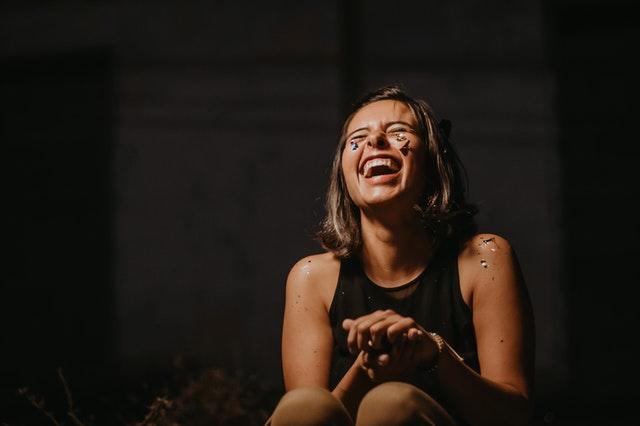 woman laughing wearing black top