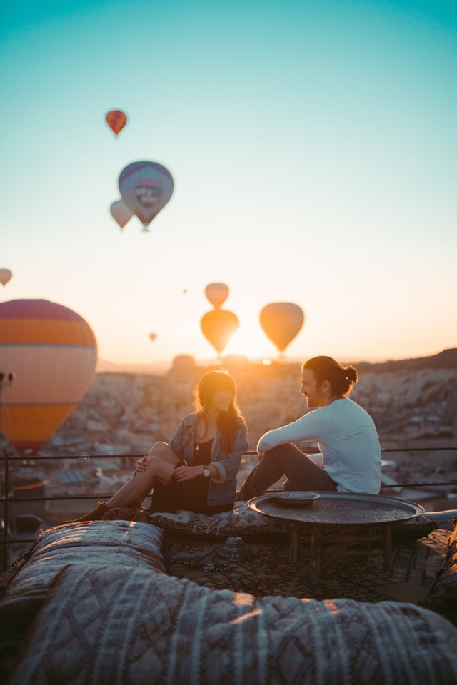 couple sitting on rooftop during sunset