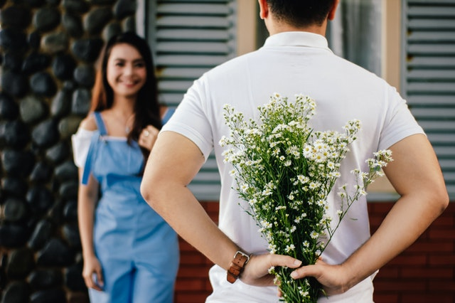 man surprising a woman with flowers