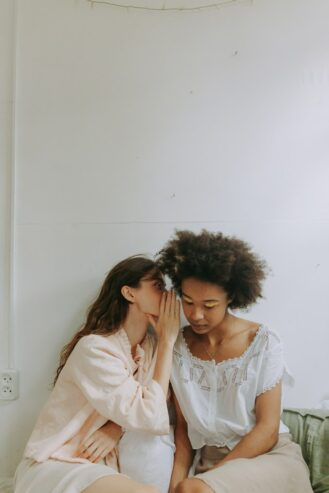 woman whispering to another woman