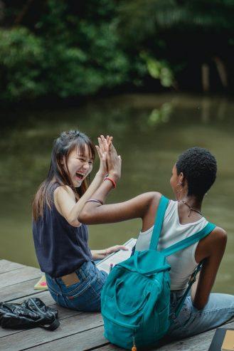 laughing women on wooden bridge