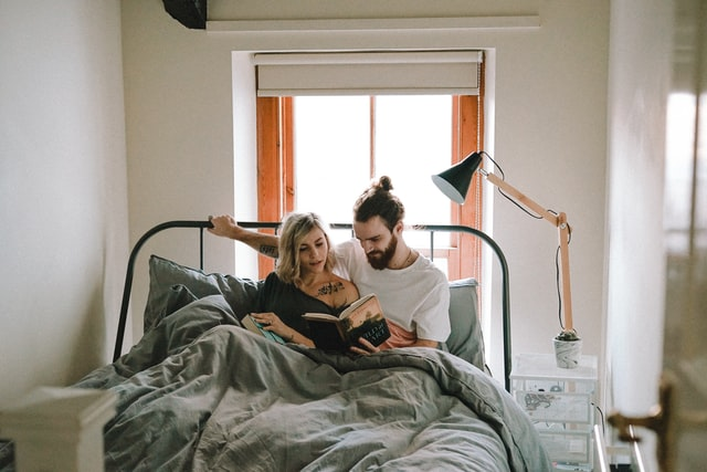couple reading book in the bed