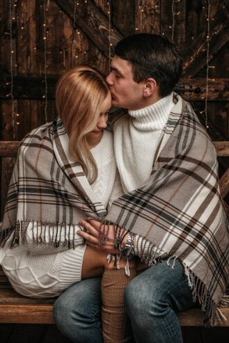 romantic couple cuddling and kissing on wooden bench