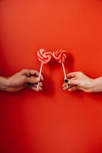 two hands holding heart shaped lollipops