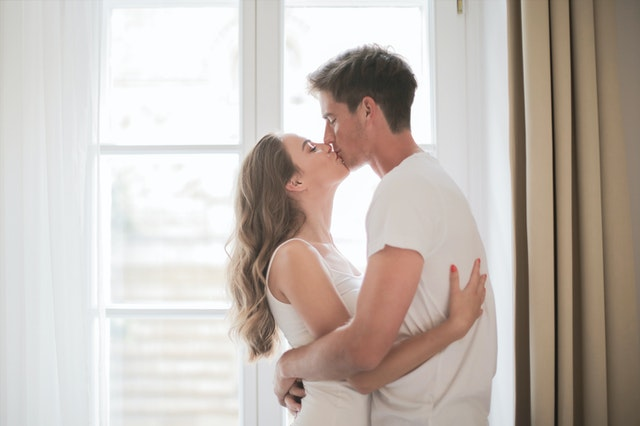 couple kissing and standing by the window