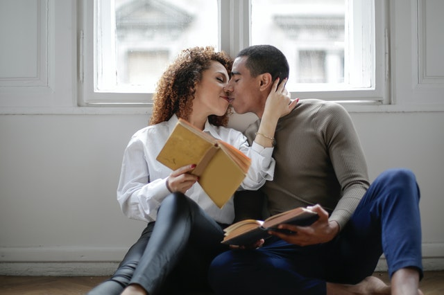couple kissing while holding books