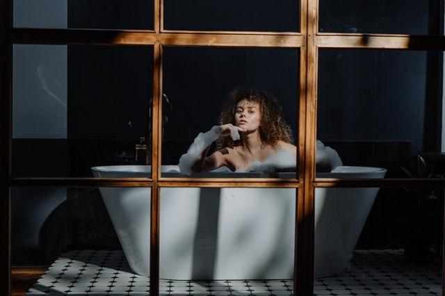 woman in black long sleeve shirt sitting on white bathtub